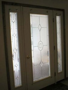 Front entry door way stained glass hand made by Tina Montgomery @ My Glass Wings Studio.  These windows features clear glass in a variety of textures with an etched glass oval initial plate in the middle and diamond bevels.