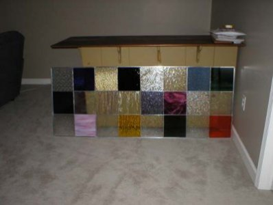Stained glass window panels custom fit for an interior window wall.  The design was made to mimick the patch work tile on the floor of a home art room.  Each square features a unique color and texture and was hand cut, foiled and soldered.  Installation may be available upon request.