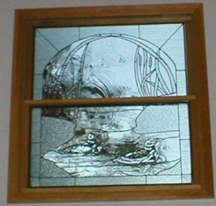 Stained glass windows custom made for house window.  Features clear glass in a variety of textures.  Glass around the ducks was selected to simulate moving water.
